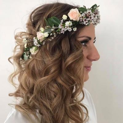 bride wearing a floral crown with long romantic curls created by Inside Hair.