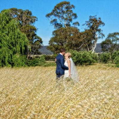 Bride and Groom hug each other in a field.
