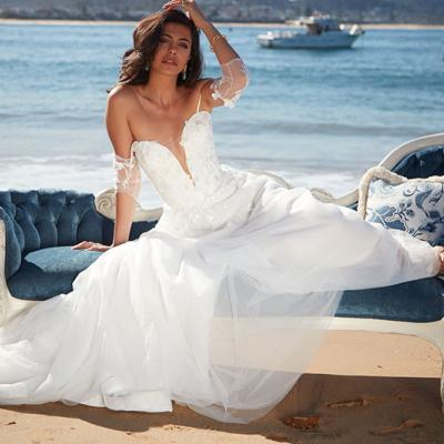 Angelina bridal gown by Sarah Joseph Couture on model sitting on a lounge on the beach.