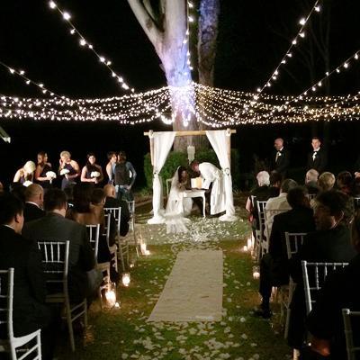 Outdoor wedding ceremony under fairylights at night.